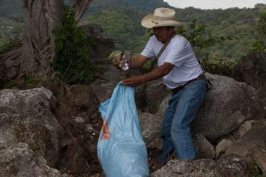 Un pescador de la zona se llena una bolsa de basura que se encuentra en las orillas del lago de Atitlán, en San Pedro La Laguna, Sololá, Guatemala. Foto: Jeff Abbott / Convite