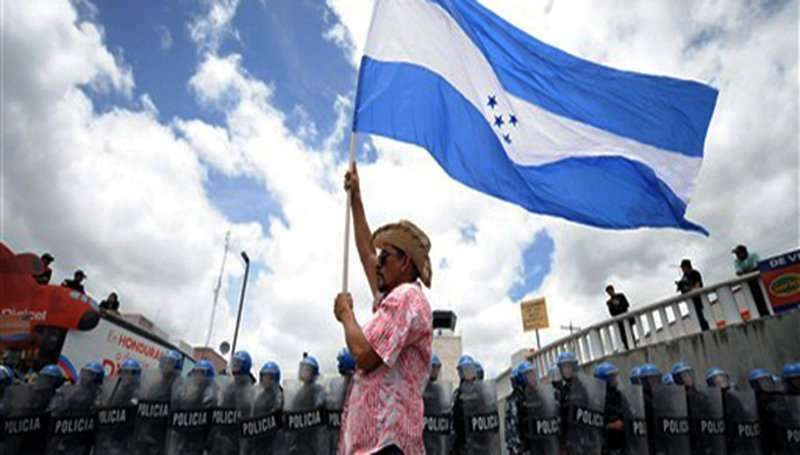 A supporter of Honduran President Manuel Zelaya holds a national flag in front of Honduran soldiers outside Toncontin international airport in Tegucigalpa on July 5, 2009. Ousted President Manuel Zelaya reaffirmed his intention to return to Honduras on Sunday, despite a threat by the interim government that it will bar his plane from landing in the country. AFP PHOTO/ Elmer MARTINEZ